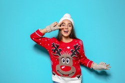 Young woman in Christmas sweater and knitted hat on color background