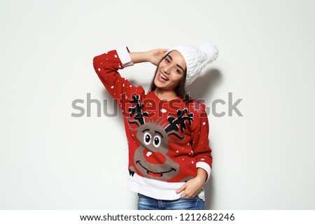 Young woman in Christmas sweater and knitted hat on white background - Shutterstock ID 1212682246
