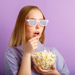 Young woman in cinema glasses watching 3d movie in cinema. Smiling teenager girl movie viewer in glasses eating popcorn isolated over purple color background with copy space. Closeup square portrait.
