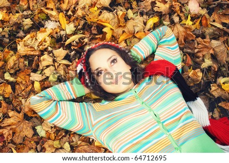 young woman in colored blouse lying on the ground with yellow leaves and hands behind head - stock photo