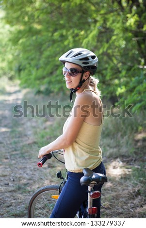 Young woman in comfortable clothing on a cycling tour through the country