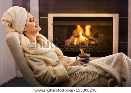 Young woman in cosy living room enjoying winter relaxation with face pack and tea, smiling.
