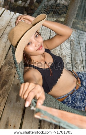 Young woman in cowboy hat resting on a hammock