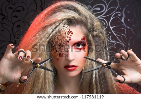 Young woman in creative image and with scissors