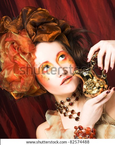 Young woman in creative image in retro style with  gold jug