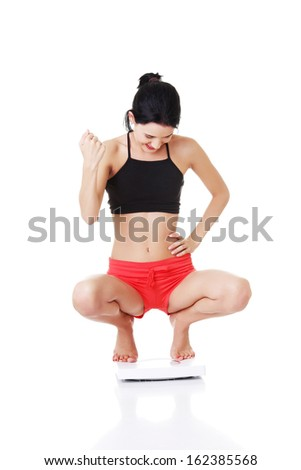 Young woman in crouch in sportswear.  Isolated on white.