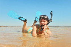 Young woman in cyan swimwear lying in shallow water on sandy shore, wearing snorkelling googles and fins, smiling
