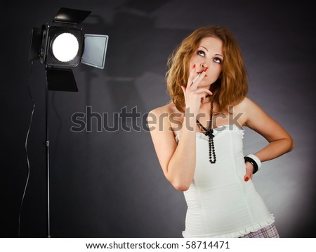 Young woman in dark studio like a backstage of photosession - stock