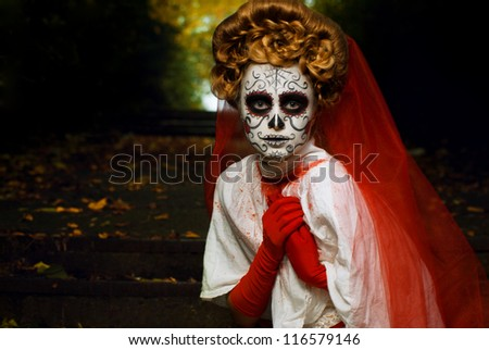 Young woman in day of the dead mask skull face art. Halloween face art