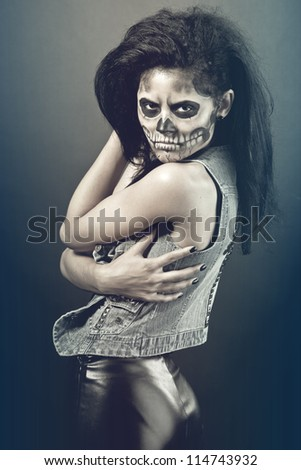 Young woman in day of the dead mask skull face art. Halloween face art with fog on black background