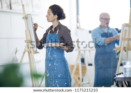 Young woman in denim dirty apron painting with paintbrush and colors in studio of arts