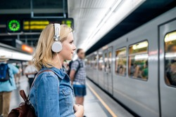 Young woman in denim shirt at the underground platform, waiting