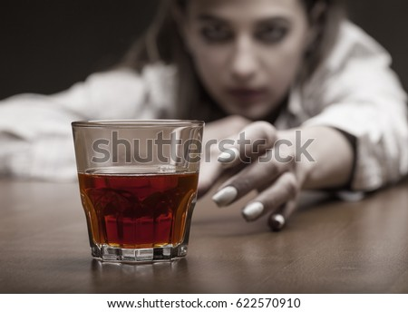 Young woman in depression, drinking alcohol on dark background. Focus on the glass