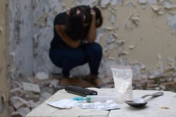 Young woman in despair suffers from narcotic effects next to packs of heroin and many drug tablets