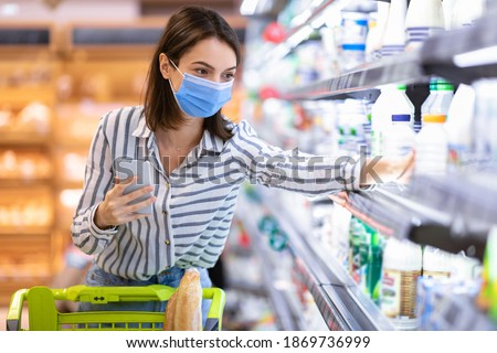 Young woman in disposable face mask taking dairy products from shelf in the supermarket, holding smartphone going through shopping list on her phone in groceries store, walking with trolley cart