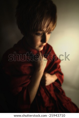 young woman in dramatic lighting trying to keep warm