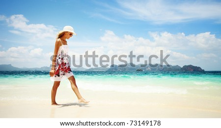Young woman in dress and straw hat walking on beach