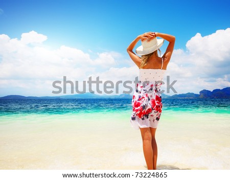 Young woman in dress holding a straw hat and looking to a blue sea