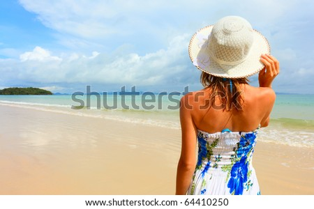 Young woman in dress standing on sand near sea and holding a hat