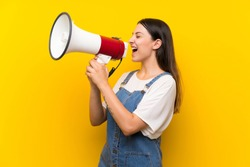Young woman in dungarees over isolated yellow background shouting through a megaphone