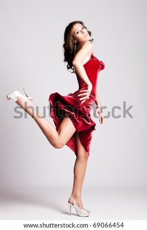 young woman in elegant red dress run, studio shot