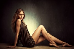 young woman in elegant short dress sit  barefoot, full body shot, studio shot