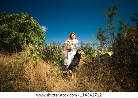 young woman in elegant silky dress with two cute dogs at countryside autumn sunny day