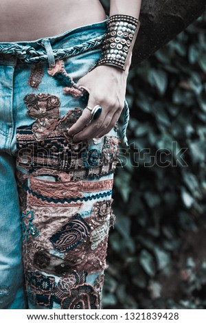 young woman in embroidered blue jeans boho style hand in pocket  summer fashion closeup