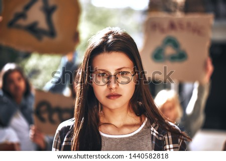 Young woman in eyewear with group of female demonstrators holding signboards while standing outdoors on the road #1440582818