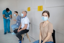 Young woman in face mask and other patients sitting in queue for covid-19 vaccination at hospital, empty space. Coronavirus vaccine, population immunization campaign concept