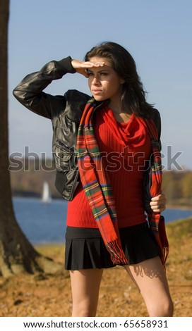 young woman in fashionable attire shielding eyes from the sun