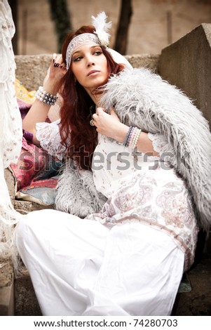 young woman in fashionable white clothes  sit on stairs, outdoor shot