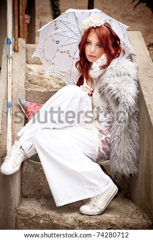 young woman in fashionable white clothes with parasol sit on stairs, outdoor shot