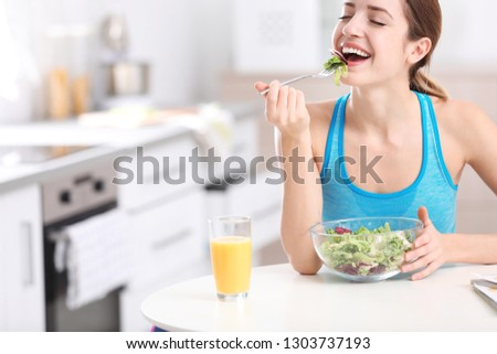 Young woman in fitness clothes having healthy breakfast at home. Space for text