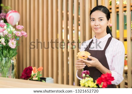 Young woman in florist workwear looking at you while sorting herberas for making floral bouquets for buyers