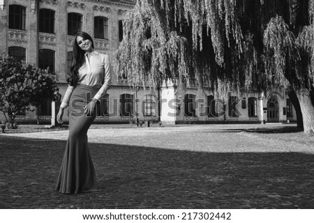 young woman in formal clothes near old university building  black and white photo