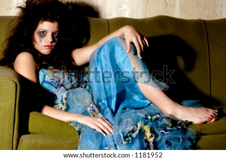 Young woman in formal dress and goth make-up sitting on old couch.