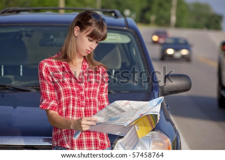 Young woman in front of a car on roadside reading a map - stock photo