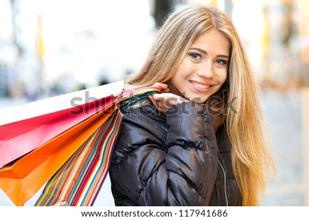 Young woman in front of a window shop and holding shopping bag