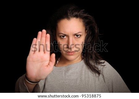 young woman in front of black background holding up her palm to say : STOP !!!