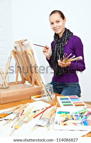 Young woman in front of easel holding brushes in her hands