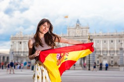 Young woman in front of Palacio de Oriente - the Royal Palace of Madrid, holding a flag with a big smile.