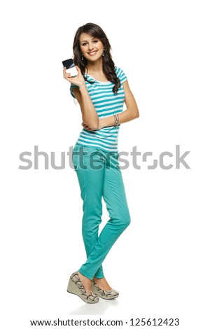 Young woman in full length showing her mobile phone / blank card with copy space, over white background