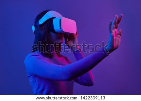 Young woman in futuristic VR headset gesturing with hand while interacting with cyberspace during education process under neon light against violet background