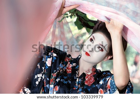 Young woman in geisha's costume raising the pink curtains