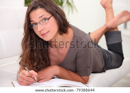 Young woman in glasses lying barefoot on the couch and writing in a book