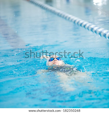 Young woman in goggles and cap swimming back crawl stroke style in the blue water indoor race pool