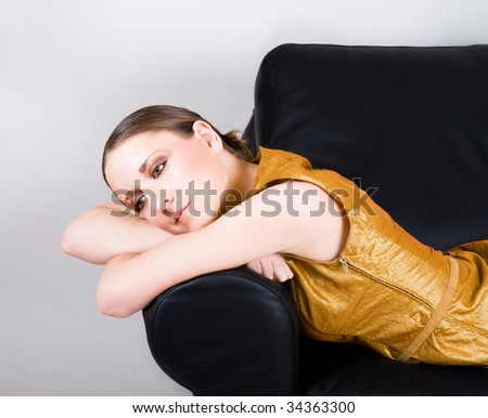 Young woman in gold dress sleep on black leather sofa