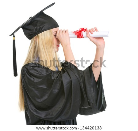 Young woman in graduation gown looking into distance through diploma