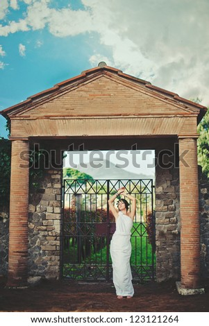 Young woman in Greek style  near old gate